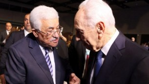 الرئيس الإسرائيلي السابق شمعون بيرس (من اليمين) يصافح رئيس السلطة الفلسطينية محمود عباس (من اليسار)  في اليوم الأول من منتدى الإقتصاد العالمي للشرق الأوسط وشمال أفريقيا 2015، الذي يُقام  في الشونة على ساحل  البحر الأحمر في الأردن، 22 مايو، 2015. (AFP/Khalil Mazraawi)