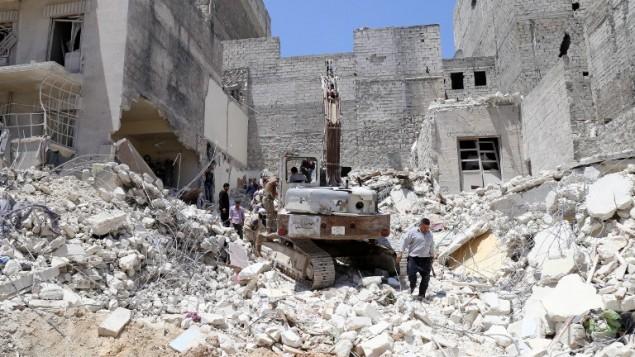 السكان يتفحصون الحطام بعد غارات من قبل قوات النظام في مدينة حلب في سوريا، 24 مايو 2015 (BARAA AL-HALABI / AFP)