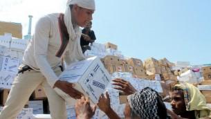 عمال يمنيون ينقلون صناديق مساعدات طبية من سفينة اماراتية تحمل 460 طن من المساعدات في ميناء مدينة عدن الجنوبية في اليمن، 24 مايو 2015 (SALEH AL-OBEIDI / AFP)