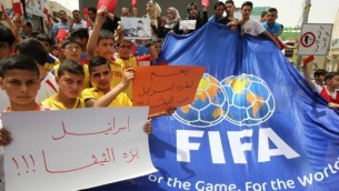 """شباب فلسطينيون يحملون لافتات حمراء كتب عليها باللغة العربية """"اسرائيل خارج الفيفا"""" خلال مظاهرة ضد الاتحاد الاسرائيلي لكرة القدم في مدينة الخليل بالضفة الغربية،  28 مايو، 2015 AFP photo/Hazem Bader"""