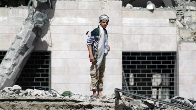 متمرد حوثي يتفحص انقاض فندق قصفه التحالف العربي بقيادة السعودية، 31 مايو 2015 (MOHAMMED HUWAIS / AFP)