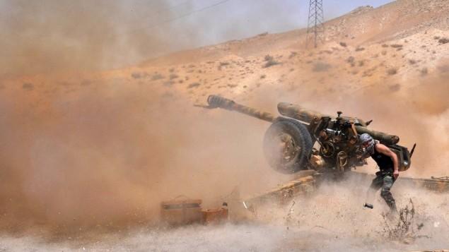 جندي سوري يطلق قذائق ضد تنظيم الدولة الإسلامية في مدينة تدمر الأثرية، 17 مايو 2015 (STR / AFP)