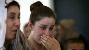 أمرأة عراقية يزيدية فرت من العنف في بلدة سنجار شمال العراق، تبكي خلال وقوفها مع آخرين في مدرسة لجأوا إليها في مدينة دهوك في إقليم كردستان بشمال العراق في 5 أغسطس، 2014. (AFP/SAFIN HAMED)