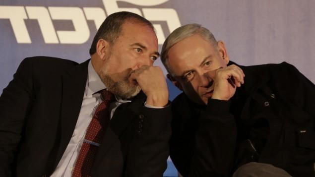 أفيغدور ليبرمان (من اليسار) وبينيامين نتنياهو (من اليمين) يتبادلان حديثا شخصيا في يناير 2013. (Tsafrir Abayov/Flash90)