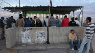 عمال بناء فلسطينيون في انتظار الدخول إلى إسرائيل، عند حاجز في مدخل مستوطنة بيتار عيليت في الضفة الغربية، 28 نوفمبر، 2010 (صورة توضيحية: Yaakov Naumi/Flash90)