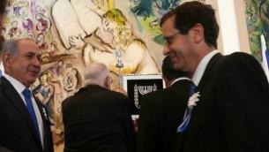 رئيس الوزراء بينيامين نتنياهو يصافح زعيم المعارضة يتسحاق هرتسوغ خلال الجلسة الإفتتاحية للكنيست في 31 مارس، 2015. (Nati Shohat/Flash90)