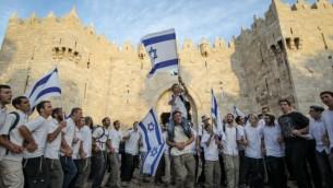 """آلاف اليهودي يلوحون بالأعلام الإسرائيلية  خلال الإحتفال ب""""يوم القدس"""" من خلال المرور في شوارع القدس، عبر  باب العامود في طريقهم إلى الحائظ الغربي في 20 مارس، 2012.  (Nati Shohat/Flash90)"""