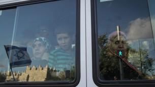 نساء عربيات يشاهدن احتفالات يوم القدس عبر شباك حافلة، 20 مايو 2012 (Nati Shohat/Flash90)
