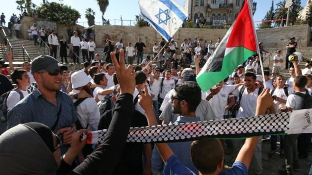 """الفلسطينيون يتظاهرون في الوقت الذي يحتفل به فتية يهود ب""""يوم القدس"""" في باب العامود بالبلدة القديمة، 17 مايو، 2015. (Nati Shohat/Flash90)"""