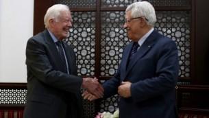 رئيس السلطة الفلسطينية محمود عباس يصافح الرئيس الأمريكي السابق جيمي كارتر خلال لقائهما في 2 مايو، 2015 في مدينة رام الله بالضفة الغربية. (AFP/Pool/Abbas Momani)