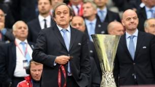 رئيس الإتحاد الأوروبي لكرة القدم ميشيل بلاتيني (من اليسار) يقف إلى جانب كأس الدوري الأوربي لكرة القدم في وارسو، بولندا في 27 مايو، 2015. (AFP/Piotr Hawale)