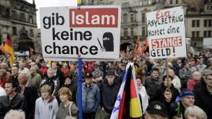 """مناصري حركة بيغيدا المعادية للإسلام يرفعون علم اسرائيل ولافتة عليها """"لا تعطوا الإسلام فرصة"""" في درسدن، 1 يونيو 2015 (JENS SCHLUETER / AFP)"""