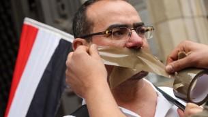 متظاهر يضع الشريط اللاصق على فمه للدلالة على حملة القمع التي تشنها السلطات المصرية ضد حرية التعبير خلال مظاهرة امام سجن في برلين حيث يحتجز الصحافي المصري احمد منصور، 22 يونيو 2015 (ADAM BERRY / AFP)