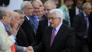 رئيس السلطة الفلسطينية محمود عباس ورئيس وزرائه رامي الحمد الله يلقون التحية على أعضاء حكومة التوافق الفلسطينية الجديدة في مدينة رام الله بالضفة الغربية، 2 يونيو، 2014. (AFP /ABBAS MOMANI)