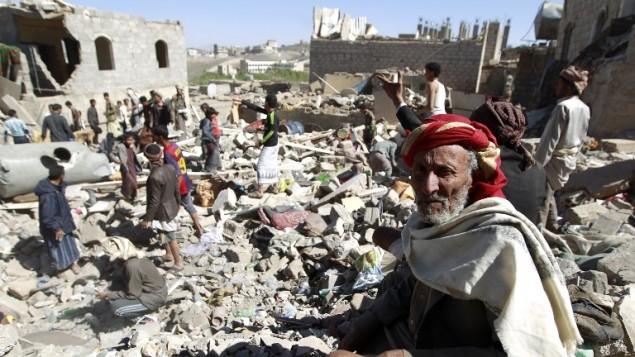 رجل يمني يجلس على الأنقاض بينما يقوم بعض الأشخاص بالبحث عن ناجين من منازل دًمرت جراء غارة جوية قادتها السعودية على منطقة سكنية في العاصمة اليمينة، صنعاء، 1 مايو، 2015. (AFP/MOHAMMED HUWAIS)