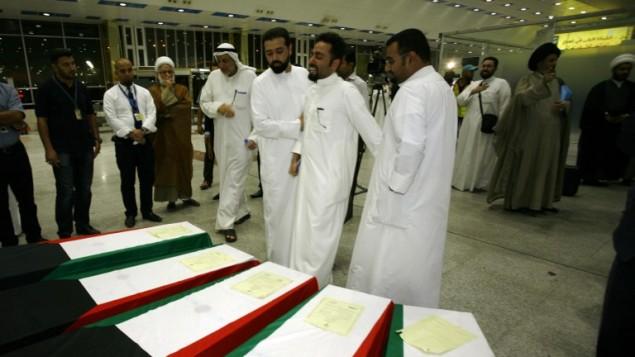 """كويتيون يتجمعون فوق جثامين أقربائهم، الذين فقدوا حياتهم خلال هجوم انتحاري على مسجد """"الإمام الصادق"""" في الكويت، عند وصول الجثامين لدفنها في مدينة النجف العراقية المقدسة، 27 يونيو، 2015. (AFP/ HAIDAR HAMDANI)"""