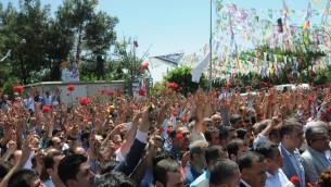 متظاهرون يحملون القرنفل في 6 يوينو، 2015، في مدينة دياربكر جنوب شرق تركيا خلال تجمعهم في محيط موقع إنفجار ناجم عن قنبلة أسفر عن مقتل شخصين وجرح المئات خلال تجمع إنتخابي لحزب كردي. ( AFP PHOTO/ILYAS AKENGIN)