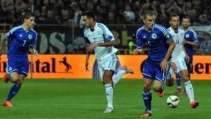 لاعب منتخب البوسنة والهرسك أونيين فرانييس (الوسط) يركض أمام لاعبي المنتخب الإسرائيلي بن ساهر (الثاني من اليسار) وعيران زهافي (الثاني من اليمين) خلال مباراة ضمن تصفيات يورو 2016 بين منتخبي البوسنة والهرسك وإسرائيل في 12 يونيو، 2015 في زينيكا. (AFP/ ELVIS BARUKCIC)