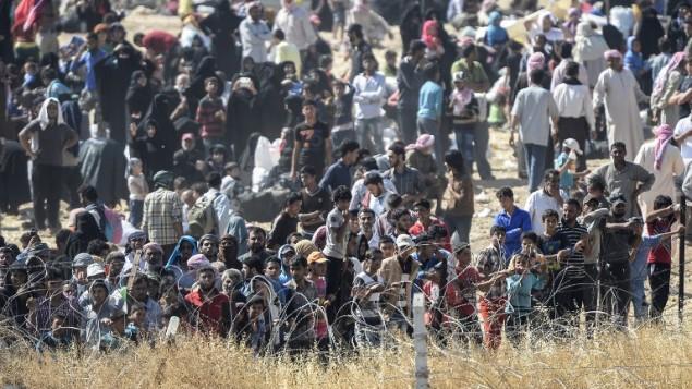 سوريون فارون من المعارك في وسط مدينة تل أبيض السورية يطلبون الحصول على ماء عند احتشادهم عند المعبر الحدودي من الجانب السوري للحدود، كما يظهرون من تركيا عند معبر أكاكاليه التركي في محافظة سانليورفا جنوب تركيا، 14 يونيو، 2015. (AFP PHOTO / BULENT KILIC)