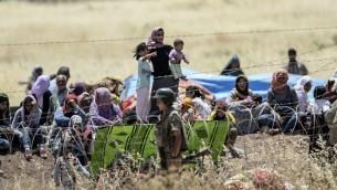 صورة مأخوذة من الجانب التركي للحدود في سوروك، محافظة سانليورفا، تظهر الجنود الأتراك وهم يحرسون الحدود في الوقت الذي ينتظر فيه أكراد سوريون وراء  السياج الشائك على الجانب السوري من الحدود بعد فرارهم من مدينة كوباني السورية، المعروفة أيضا بعين العرب، 26 يونيو، 2015.  (AFP PHOTO/BULENT KILIC)