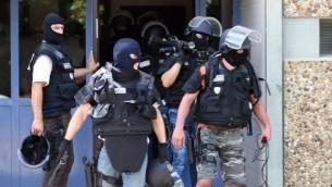 قوات خاصة فرنسية  تغادر المبنى الذي يضم شقة الرجل المشتبه بتنفيذ الهجوم في سان بريست بالقرب من ليون، 26 يونيو، 2015. (AFP PHOTO / PHILIPPE DESMAZES)