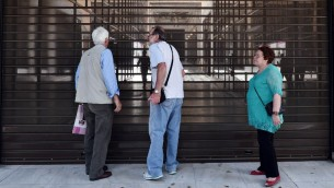 متقاعدون يقفون امام ابواب مصرف مغلق في مركز اثينا، اليونان، 29 يونيو 2015 (LOUISA GOULIAMAKI / AFP)