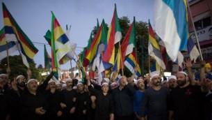 دروز إسرائيليون يلوحون بالأعلام خلال تظاهرة شارك فيها حوالي 2000 شخص في بلدة دالية الكرمل، دعوا فيها الحكومة الإسرائيلية إلى دعم ومساعدة أقربائهم في سوريا، 14 يونيو، 2015. (AFP/MENAHEM KAHANA)