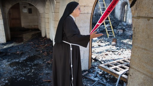 راهبة تتفحص اضرار الحريق في كنيسة الطابغة على ضفاف بحيرة طبريا في اسرائيل، 18 يونيو 2015 (MENAHEM KAHANA / AFP)