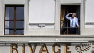 """صورة توضيحية: وزير الخارجية الأمريكي جون كيري يقف أمام  نافذة غرفته في فندق """"بو-ريفاج بالاس"""" خلال إستراحة في محادثات إيران النووية في لوزان بسويسرا. 1 ابريل، 2015. ( AFP PHOTO / FABRICE COFFRINI)"""