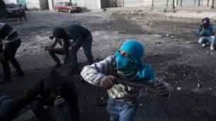 شباب فلسطينيون يرشقون الحجارة خلال مواجهات مع شرطة الحدود الإسرائيلية في مخيم شعفاط في القدس الشرقية، 7 نوفمبر 2014 (Yonatan Sindel/Flash90)