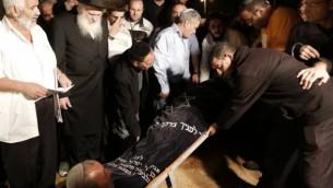 مشيعون يقومو بإنزال جثمان آرون سمادجا، أحد القتلى الإسرائيليين الثلاثة جراء سقوط صاروخ تم إطلاقه من غزة، خلال جنازته في مقبرة في مدينة كريات ملئاخي الجنوبية، الثلاثاء، 15 نوفمبر، 2012. (Tsafrir Abayov/Flash90)