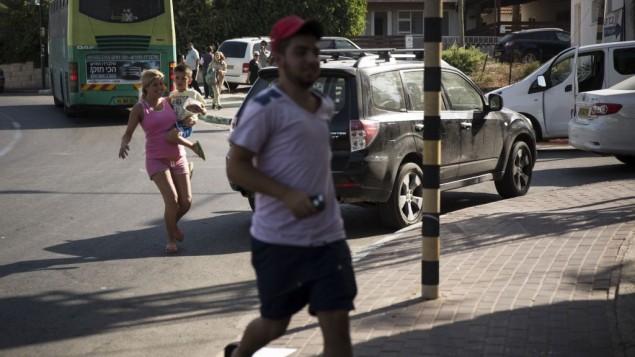 """إسرائيليون يهرعون للملاجئ عند سماع صفارات الإنذار في سديروت، جنوب إسرائيل، في اليوم الثالث من عملية """"الجرف الصامد""""، الخميس 10 يوليو، 2014. (Hadas Parush/Flash90)"""