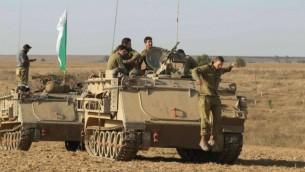 """جنود إسرائيليون بالقرب من حاملة جنود مدرعة عند الحدود الجنوبية لإسرائيل مع غزة، في اليوم الثامن من عملية """"الجرف الصامد"""". 15 يوليو، 2014. ( Yossi Aloni/Flash90)"""