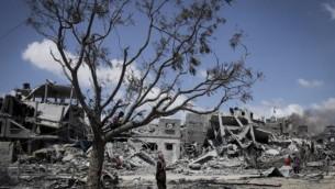 فلسطينيون يبحثون عن ممتلكاتهم بين الطام بعد غارة اسرائيلية في بيت لاهيا، شمال قطاع غزة، 4 اغسطس 2014 (Emad Nasser/Flash90)