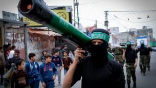 نشطاء ملثم في حركة حماس يعرض صاروخ خلال مسيرة لإحياء الذكري ال27 لتأسيس الحركة، في مخيم النصيرات للاجئين وسط غزة في 12 ديسمبر، 2014. ( AFP/ SAID KHATIB)