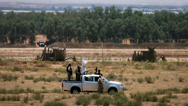 مقاتلون فلسطينيون من كتائب عز الدين القسام، الجناح المسلح لحركة حماس، يجولون في المنطقة المجاورة للحدود مع اسرائيل بالقرب من رفح جنوب القطاع، 3 يونيو 2015 (Abed Rahim Khatib/Flash90)