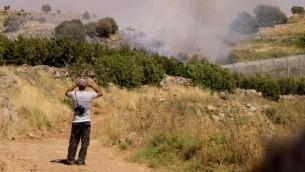 رجل درزي يراقب تبادل النيران بين القوات السورية من الطرف الإسرائيلي من الحدود في هضبة الجولان، 16 يونيو 2015 (Basel Awidat/Flash90)