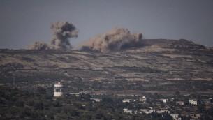 صورة التقطت من الطرف الإسرائيلي لهضبة الجولان تظهر الانفجارات الناتجة عن القتال بين فصائل سورية في بلدة حضر في الطرف السوري للجولان، 16 يونيو 2015 (Basel Awidat/Flash90)