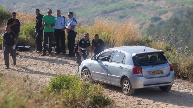 عناصر الأمن الإسرائيلي يقفونبجانب مركبة تابعة للضحايا الإسرائيليين في هجوم نفذه مسلح فلسطيني بالقرب من مستوطنة دوليف في الضفة الغربية، 19 يونيو. (Flash90)