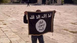 """فتى يحمل علم """"الدولة الإسلامية"""" في الحرم القدسي في أغسطس 2014. (Facebook)"""