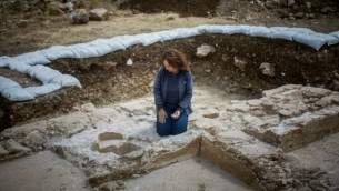 أنيت ناغار من سلطة الآثار الإسرائيلية تلقي نظرة على جرن المعمودية لكنيسة من الفترة البيزنطية تم إكتشافها بالقرب من أبو غوش خلال عمليات توسيع لطريق القدس-تل أبيب السريع، يونيو 2015. (Yonatan Sindel/Flash90)