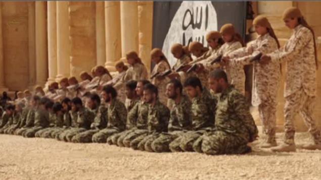 صورة شاشة لشريط نشره تنظيم الدولة الإسلامية يظهر اعدام 25 من جنود القوات السورية النظامية بايدي فتيان وسط اثار مدينة تدمر (YouTube)