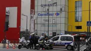 سيارات الشرطة امام المتجر الفرنسي التي تعرض للسطو المسلح، 13 يوليو 2015 (THOMAS SAMSON / AFP)