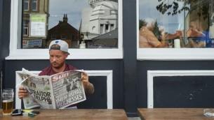 """رجل يقرأ صحيفة """"ذي صن"""" الفضائحية البريطانية وعلى صفحتها الأولى صورة للملكة اليزابيث وهي طفلة تقوم بالتحية النازية، 18 يوليو 2015 (NIKLAS HALLE'N / AFP)"""