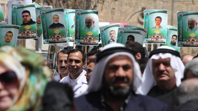 صور اعضاء في حركة حماس المسجونين في السجون الإسرائيلية خلال مظاهرة في الخليل، 15 ابريل 2015  (AFP PHOTO/HAZEM BADER)