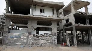 اطفال فلسطينيون بجانب منزلهم المدمر الذي وضع داخله ثلاث غرف جاهزة في حي الشجاعية في غزة، 11 مايو 2015 (THOMAS COEX / AFP)