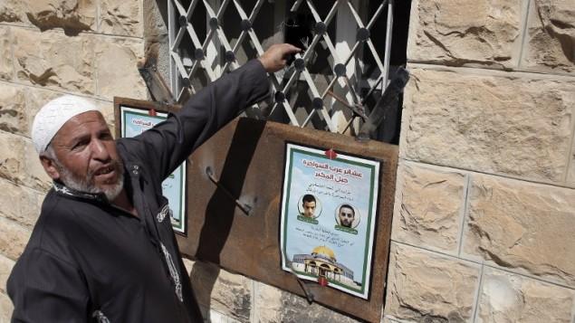 احد اقرباء اولاد العم غسان وعدي ابو جمل يقف بجانب منزل عائلة عدي ابو جبل في حي جبل المكبر في القدس الشرقي بعد ان اغلقت قوات الأمن الإسرائيلية شبابيك وابواب المنزل بقضبان حديد، 1 يوليو 2015 (AHMAD GHARABLI / AFP)