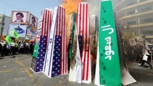 متظاهرون إيرانيون يحرقون الإعلام الإسرائيلية والأمريكية والسعودية خلال تظاهرة  بمناسبة يوم القدس العالمي في طهران، 10 يوليو، 2015. (AFP PHOTO / ATTA KENARE)