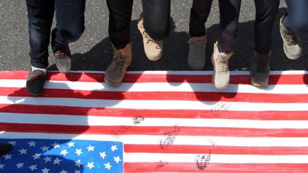 متظاهرون إيرانيون يدوسون على العلم الأمريكي خلال تظاهرة  بمناسبة يوم القدس العالمي في العصمة العراقية بغداد، 10 يوليو، 2015. (AFP PHOTO / AHMAD AL-RUBAYE)