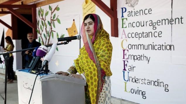 صورة اصدرها صندوق ملالا تظهر الحائزة على جائزة نوبل للسلام ملالا يوسفزاي تلقي خطابا بعيد ميلادها ال18 بينما تفتتح مدرسة جديدة للبنات في لبنان للاجئات سوريات، 12 يوليو 2015 (MALIN FEZEHAI / MALALA FUND / AFP)